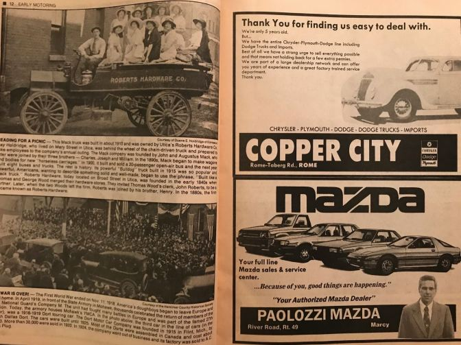 Magazine with photos of cars from the 1900s and 1920s on left, with car ads on the right for Copper City Chrysler Dodge Plymouth on top and Paolozzi Mazda on the bottom right.