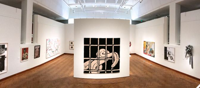 Panorama of ground level gallery, with a large drawing of an octopus tentacle behind a prison cell in the middle of the room.