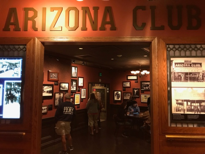 Exterior of hotel room with the words ARIZONA CLUB across the top of the doorway. The view through the open doorway shows a replica casino with pictures hanging on the wall.