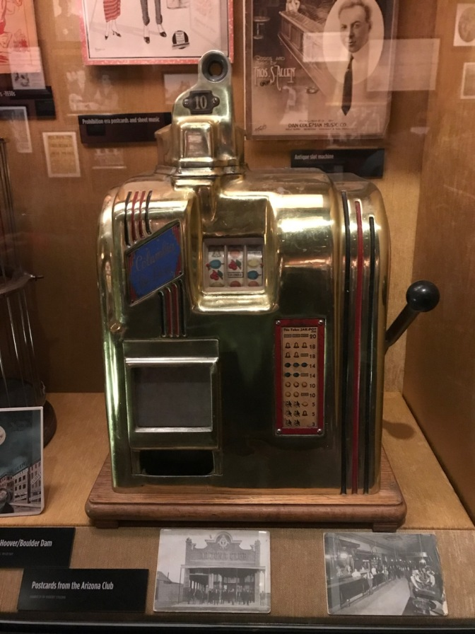 Columbia Deluxe slot machine in glass display case, surrounded by photographs.