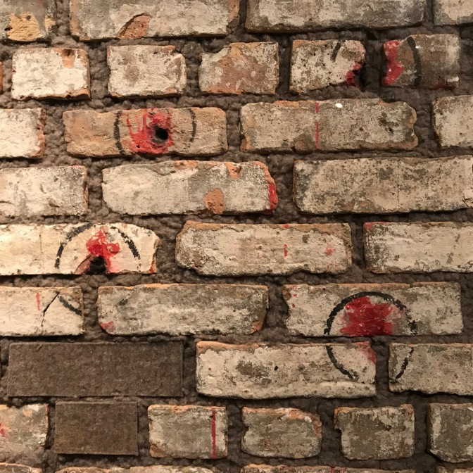 Brick wall with four bullet holes in it, with red stains around the wall.