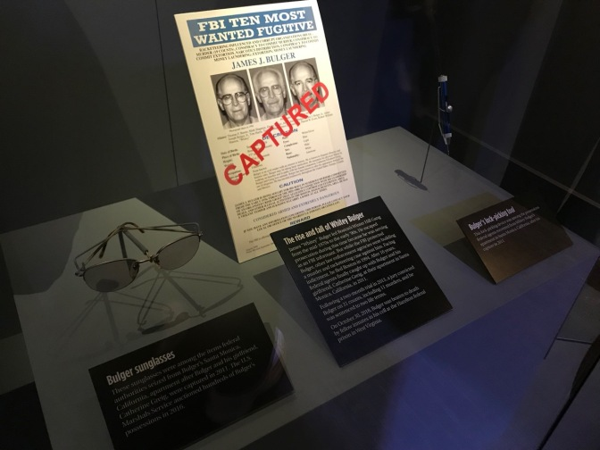 FBI TEN MOST WANTED FUGITIVE poster for James J. Bulger, along with Bulger's sunglasses and his lock-picking tool.
