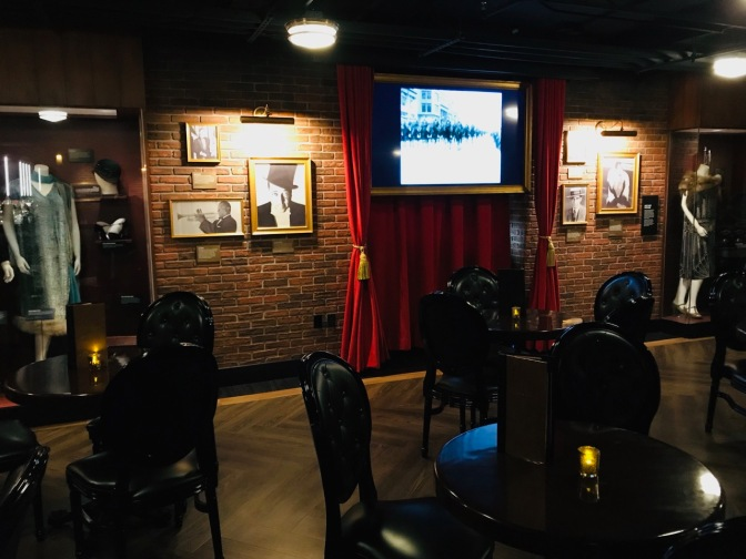 """Basement speakeasy bar, with brick walls. Items from the 1920s adorn the walls, including """"flapper"""" dresses."""