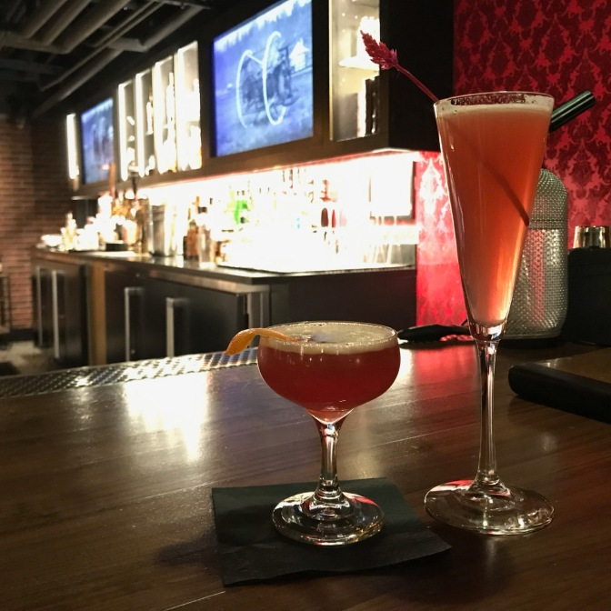 Long stem glass with cocktail, and shorter rounded glass with cocktail on bar.