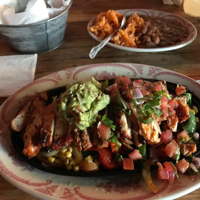 Plate with chicken, pico de gallo, guacamole, and peppers. In the background is another plate with rice and beans.