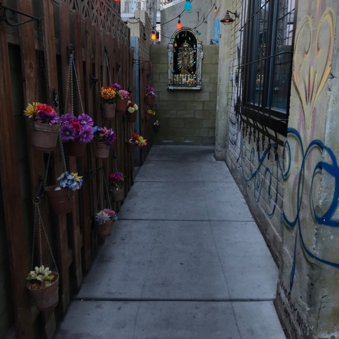 Exterior entrance of La Comida. A small shrine to Mary is located in a grotto in a wall, and plants hang from a wooden fence.