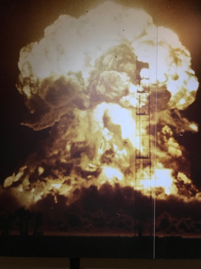Photograph of mushroom cloud, mounted on a wall.
