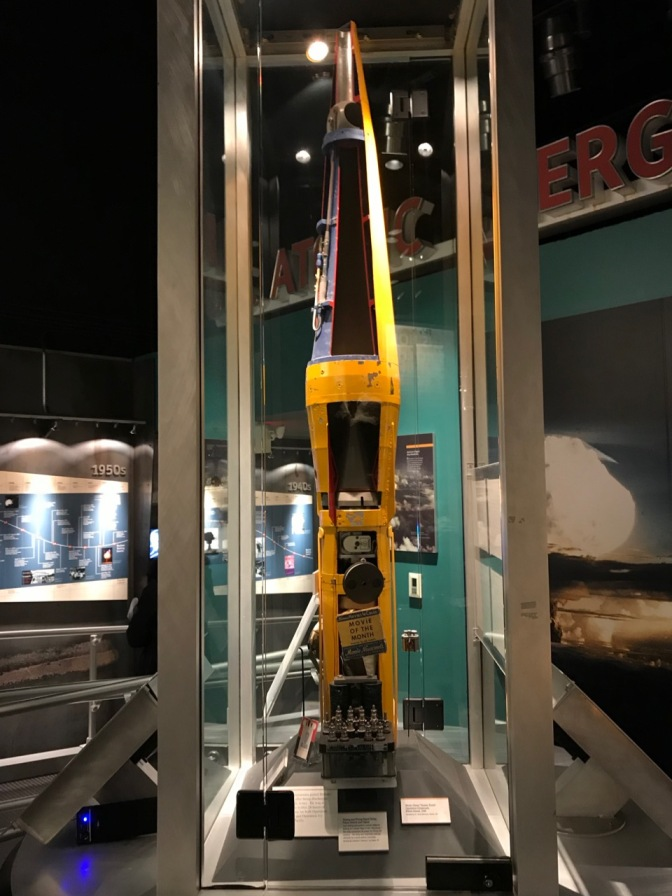 Yellow rocket, with panels removed, behind glass case.