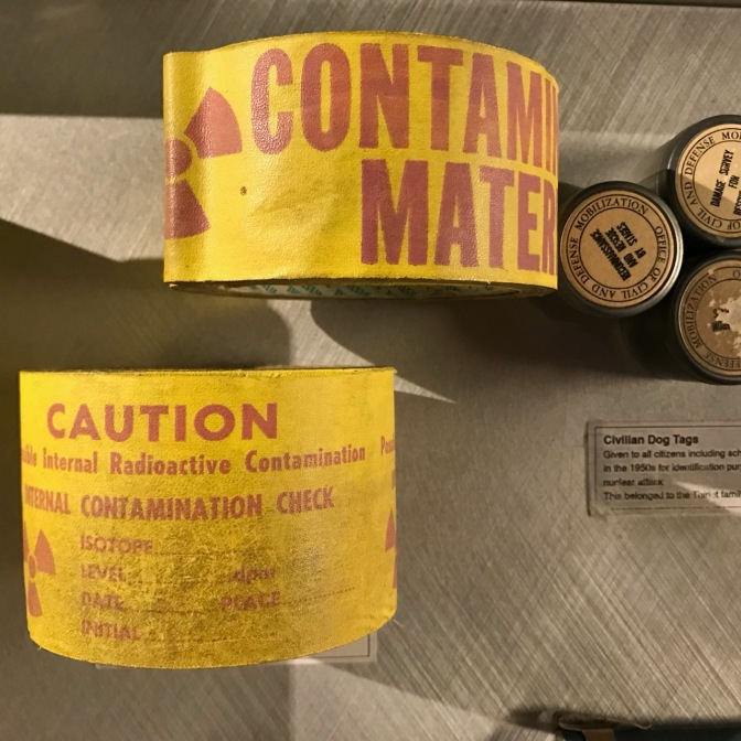 Caution tape and civilian dog tags. The caution tape says CONTAMINATED MATERIAL CAUTION INTERNAL RADIOACTIVE CONTAMINATION.
