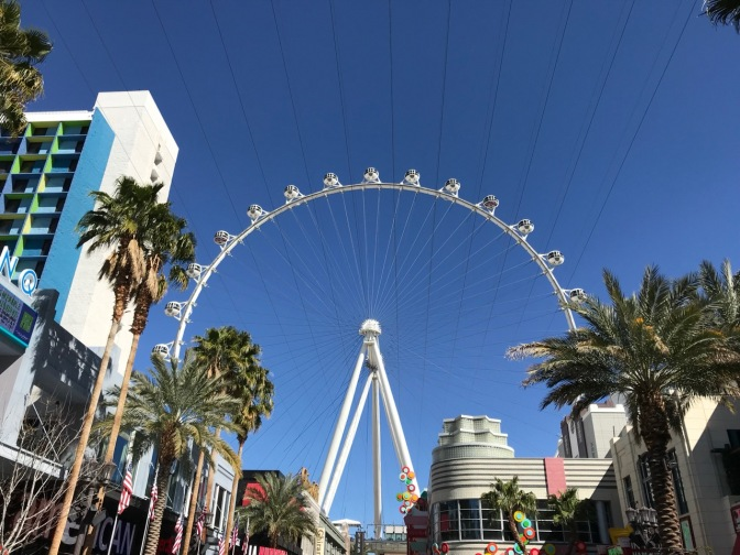 White Ferris Wheel towering over buildings on the strip.