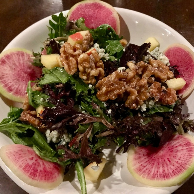 View of Therapy Signature Salad, with walnuts, greens, and watermelon radishes.