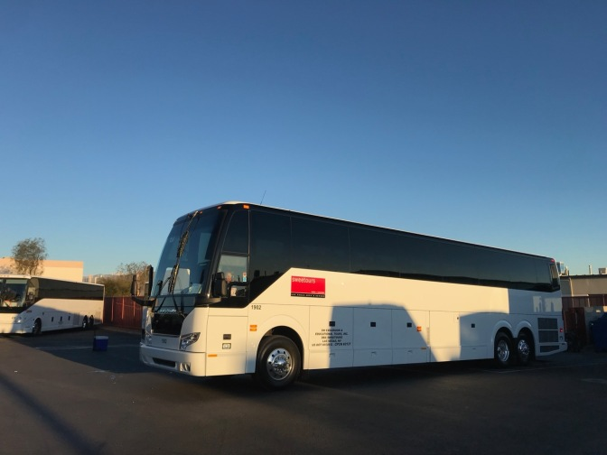 White and black tour bus in a parking lot.