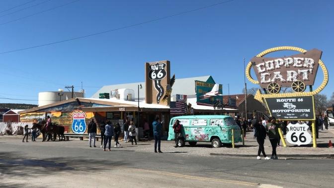 Copper Cart tourist shop in Seligman, Arizona. Tourists amble about outside.