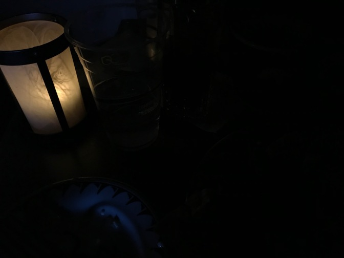 View of candle in blackened room.