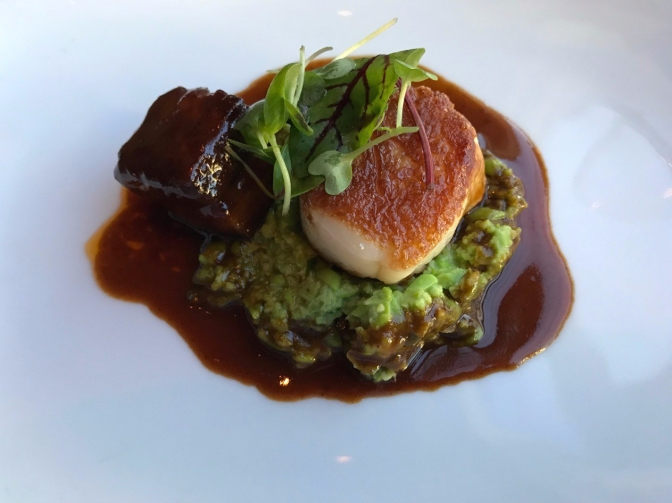 Scallop and pork belly on a bed of sweet pea and scallop sherry au jus.