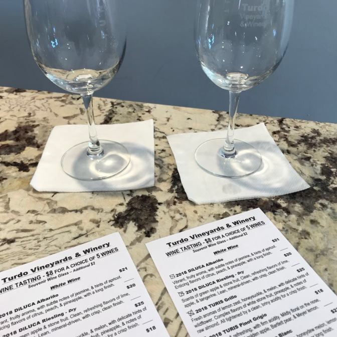 Two wine glasses on bar top with tasting menus in the foreground.