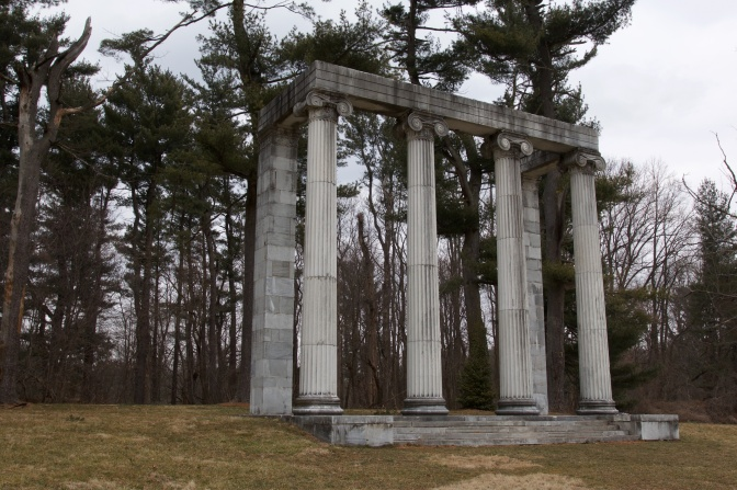 The Colonnade, a structure of four columns and two stone pillars, by the tree line.