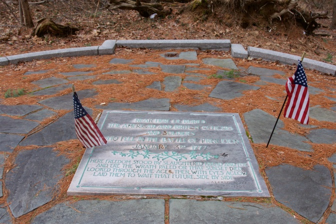 Grave marker memorial for unknown soldiers, surrounded by two American flags. A circle of stones surrounds the marker.
