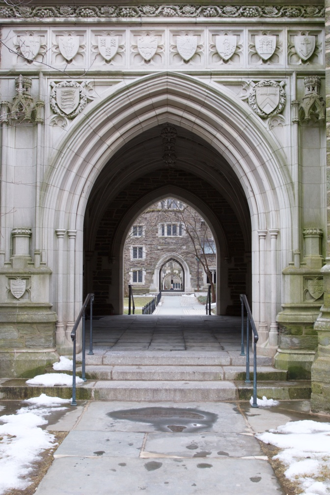 Gothic archway through building, looking at campus beyond.