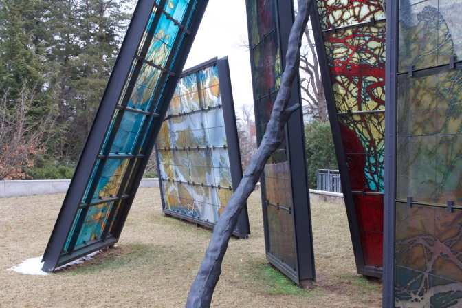 Stained glass windows in black metal panels on lawn outside of museum.