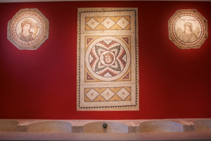 Three Roman mosaics on a red well.