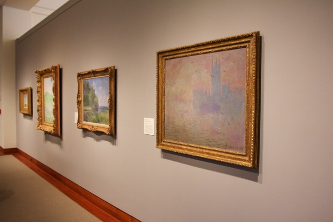 Gallery with four impressionist paintings on the wall.