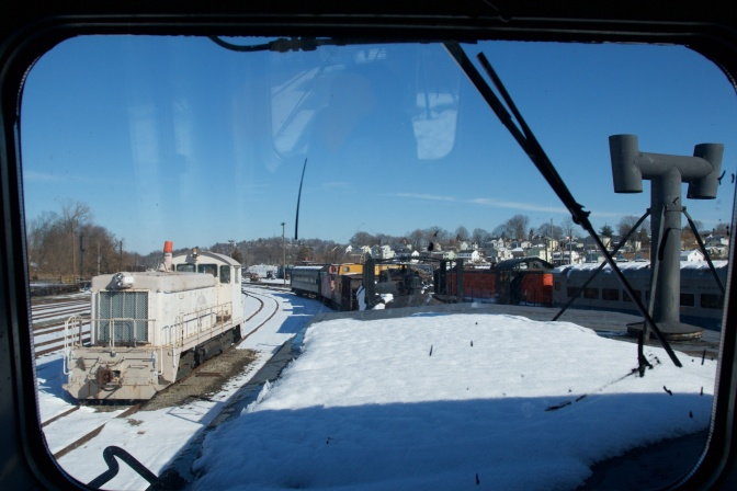 View of rail yard through upper windows of caboose. Numerous trains are visible.