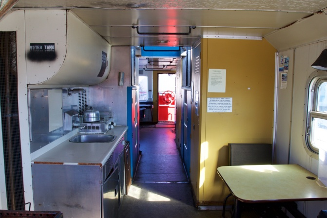Interior of caboose, with counter and sink on right and table with chair on left.