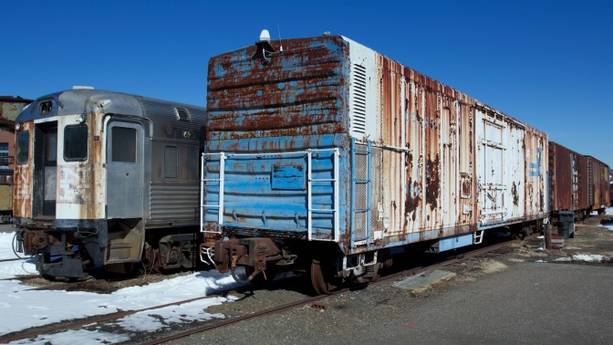 Freight cars and passenger cars with rusting and fading paint.