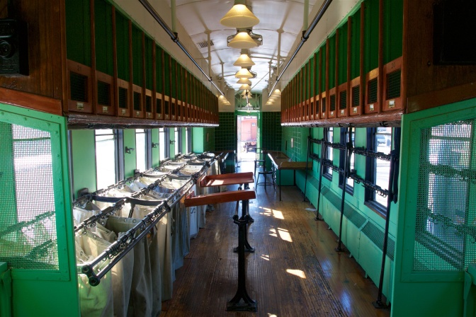 Interior of postal car, with sacks hanging in bins on the left, lockers above in the luggage rack, and post office boxes in the background.