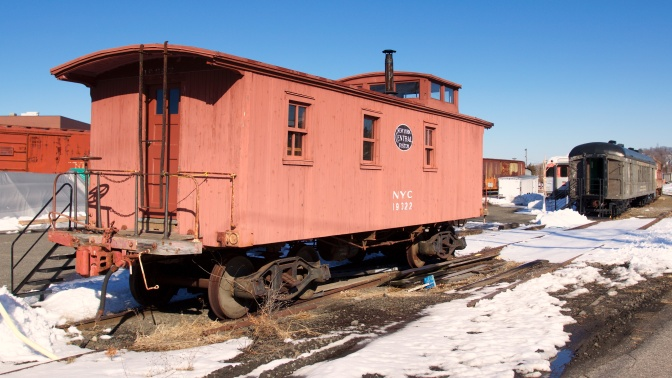 Red wooden caboose with NYC 19322 on the side.