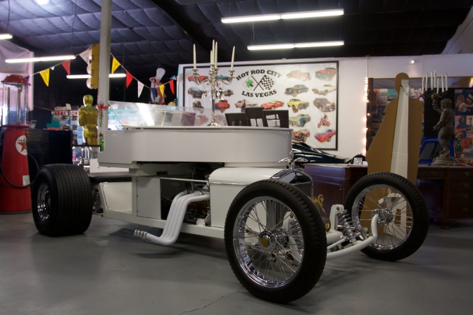 White piano on a roadster frame with racing engine and wheels.