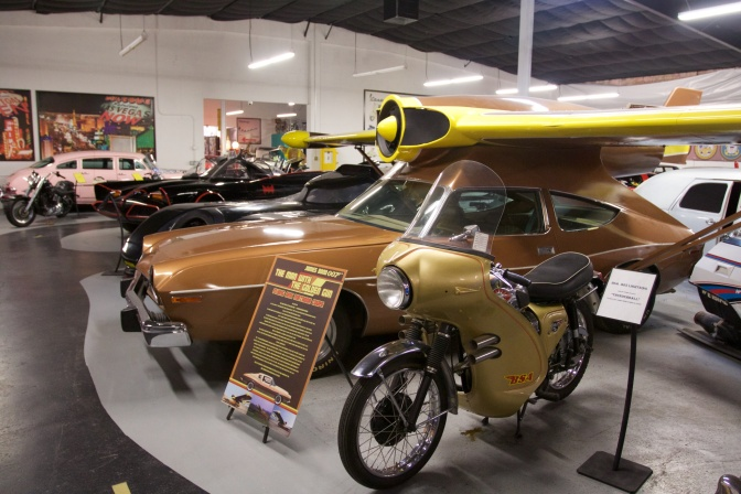 Gold MAC Matador with yellow jet engine and wings on top of vehicle.