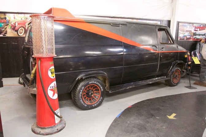 Exterior of black and grey van with orange stripe. A Texaco gas pump is in the foreground.