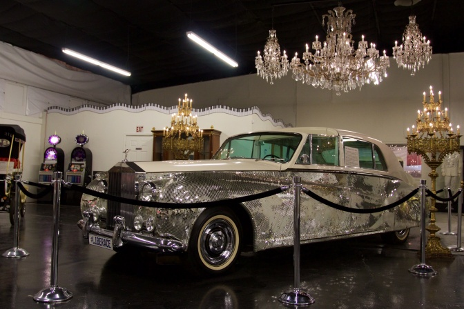 Rolls Royce Phantom V, covered in rhinestones. Several chandeliers hang from the ceiling.