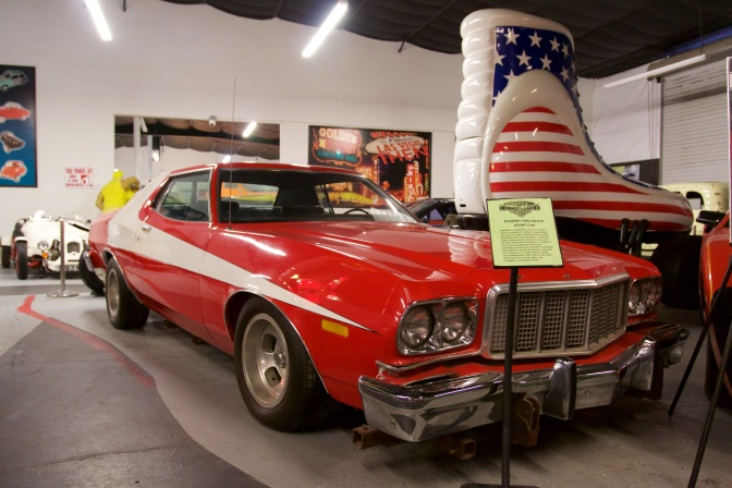 Red and white Ford Torino with Roller Skate hot rod in background.
