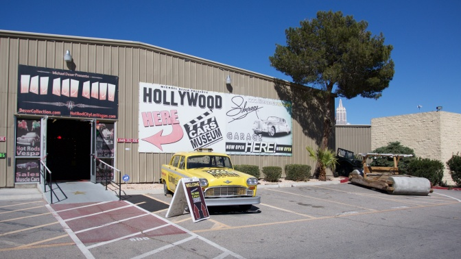Exterior of Hollywood Cars Museum, with a yellow cab and the Flinstone's car parked in front of the building. A large sign says HOLLYWOOD CARS MUSEUM HERE.
