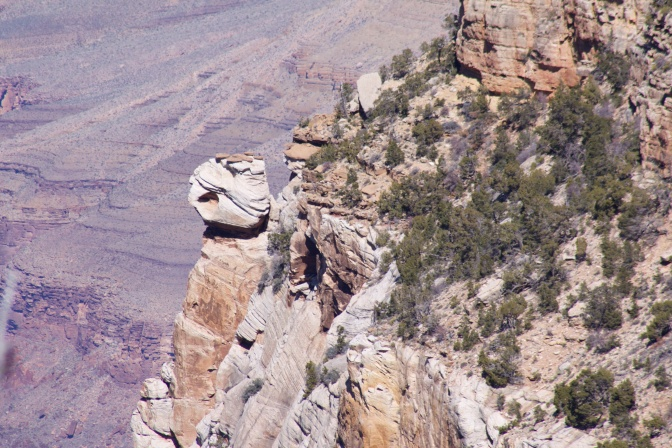 Boulder perched on side of cliff.