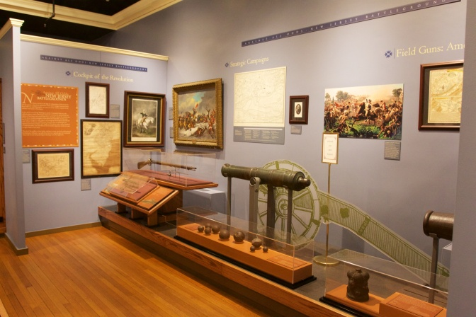 Interior of museum, with an exhibit on cannons and rifles from the Revolutionary War.
