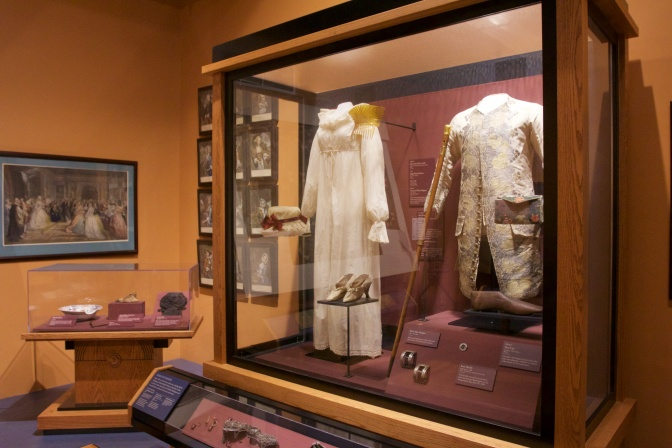 Glass case with dress attire of George and Martha Washington.