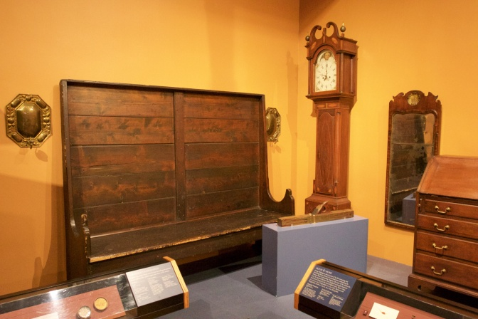 Collection of household goods including a grandfather clock, a high-backed bench, and a mirror.