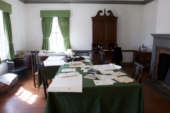 Field office of George Washington, with maps and orders on the tables. A fireplace is on the right of the image. And two windows are on the left.