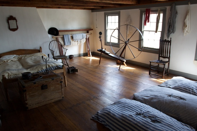 Servants quarters, with a bed, several bunks and a spinning wheel.