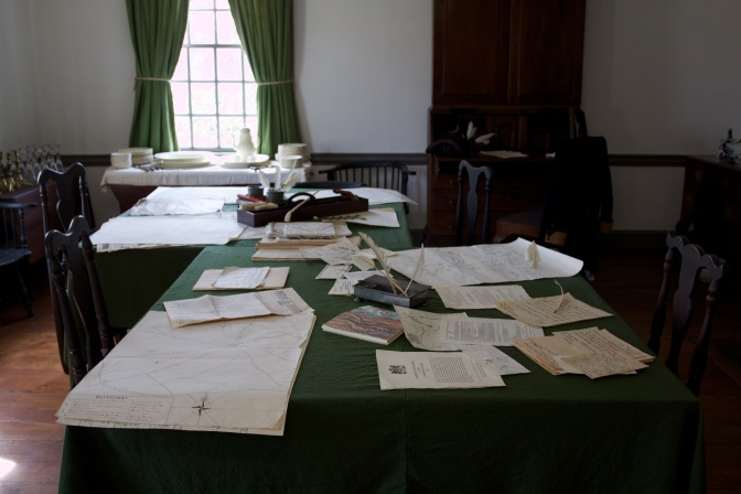 Tables with orders and maps. A window is in the background.