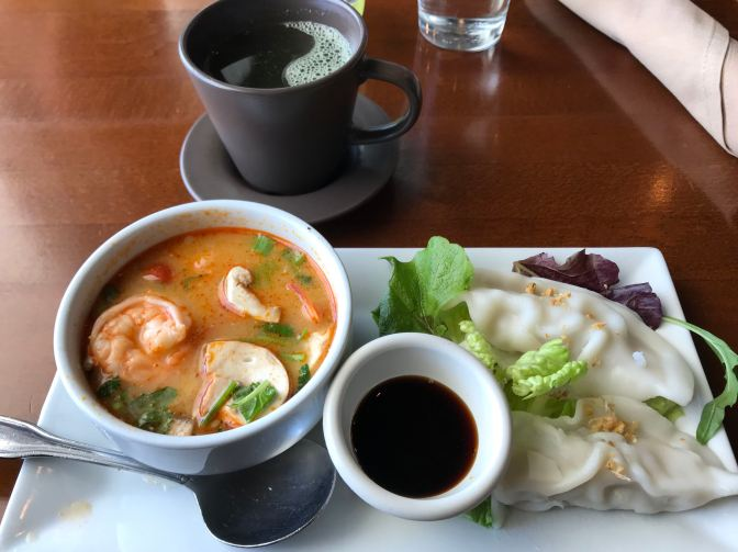 White rectangular plate with bowl of tom yum soup, a smaller bowl of soy sauce, and two pork dumplings.