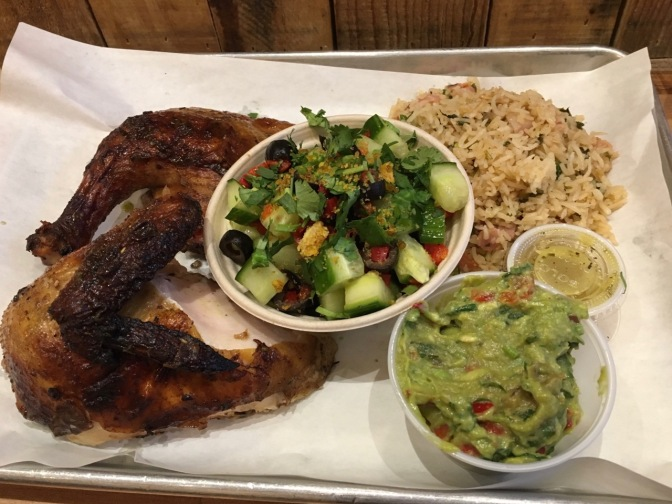 Half chicken, rice, cucumber salad, and guacamole, on a metal tray with a paper liner.