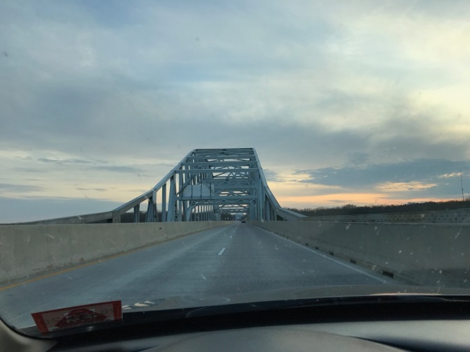 View of bridge through car windshield, with clouds in the distance.
