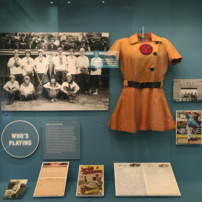 Exhibit on women in baseball, including uniform, magazines, and a photo of a women's baseball team.