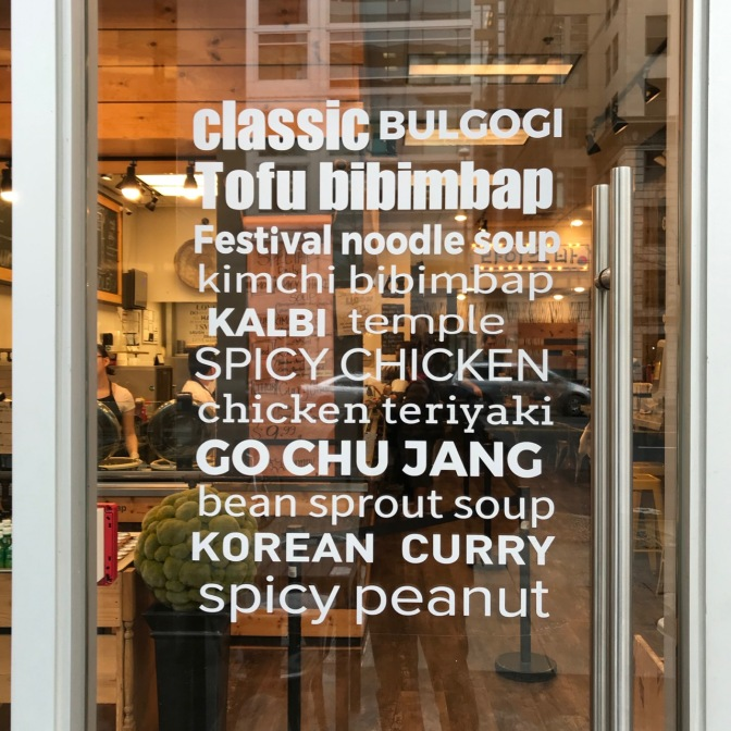 Glass door with words CLASSIC BULGOGI TOFU BIBIMBAP FESTIVAL NOODLE SOUOP KIMCHI BIBIMBAP KALBI TEMPLE SPICY CHICKEN CHICKEN TERIYAKI GO CHU JANG BEAN SPROUT SOUP KOREAN CURRY SPICY PEANUT