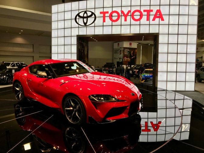 Red Toyota Supra on black pedestal, with Red Toyota sign in the background.